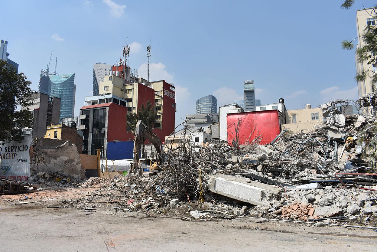 """Este fin de semana finalizó la demolición del edificio de Puebla 277 en la Colonia Roma Norte de la delegación Cuauhtémoc, el cual resultó dañado con el pasado sismo del 19 de septiembre, así lo informó la Secretaría de Obras y Servicios (Sobse) de la Ciudad de México. Los trabajos concluyeron de forma manual y con maquinaria, la Sobse demolió en 50 días toda la estructura del inmueble. El edificio que operaba como call center de una empresa telefónica, contaba con cuatro niveles y cuartos de azotea que tras el sismo presentaron daños en las columnas, las cuales daban soporte a las trabes y losas de concreto reforzado. Ante la situación, el Comité de Emergencias de la Ciudad de México dictaminó la demolición por representar riesgo tanto para los edificios colindantes como para la población. Edgar Tungüí Rodríguez, titular de la dependencia, destacó la importancia de disminuir los riesgos en inmuebles con daño estructural, como parte de la Reconstrucción de la Ciudad de México. """"La calle de Puebla fue de las más afectadas durante el movimiento telúrico del 19 de septiembre, ya que tres edificios presentaron daños estructurales o colapsos parciales. Los inmuebles ya han sido demolidos en su totalidad. Por ello en los próximos días se reabrirá la circulación en las calles de Puebla y Ocotlán"""", señaló Edgar Tungüí. La demolición comenzó con el retiro de pertenencias, equipos de cómputo, instalaciones, entre otras, para después colocar un tapial de madera y apuntalar los cuatro niveles, y así dar paso al proceso de demolición. Para los cuartos de azotea fue de forma manual con la ayuda de picos, mazos, palas y martillos demoledores de concreto. Finalmente, con la ayuda de maquinaria pesada como la retroexcavadora con cizalla, permitió el retiro de pedazos grandes de losa, trabes y muros de los cuatro niveles. Las siguientes actividades consistirán en la limpieza del terreno y el traslado de escombro así como la colocación del tapial de madera para resguardar el ligar. La"""